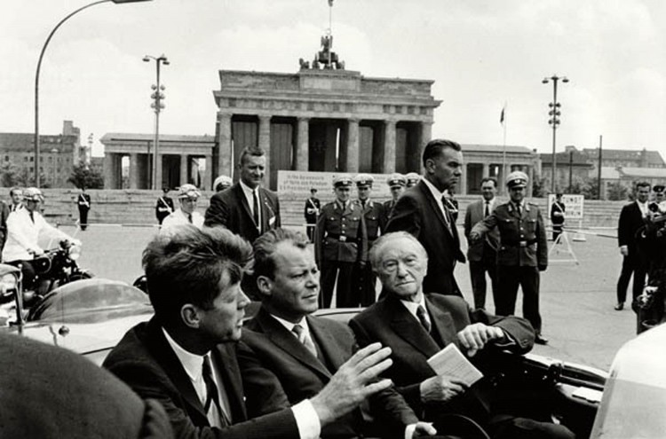 ORG XMIT: 131301_1.tif In this photo released by he Kennedy Museum, President John F. Kennedy, left, Willy Brandt, center, then mayor of West Berlin, and West German Chancellor Konrad Adenauer, right, ride in a car at the Brandenburg Gate on June 26, 1963. The day Kennedy visited Berlin, Klaus Schuetz sensed something special was happening as he waited in city hall for the president's arrival. Thousands of people chanting Kennedy's name lined the motorcade route and the square outside. For people of Schuetz's generation, the emotion of that eight-hour visit, on June 26, 1963, lingers after more than 40 years. (AP Photo/Will McBride-Camera Work, Kennedy Museum) **MANDATORY CREDIT**